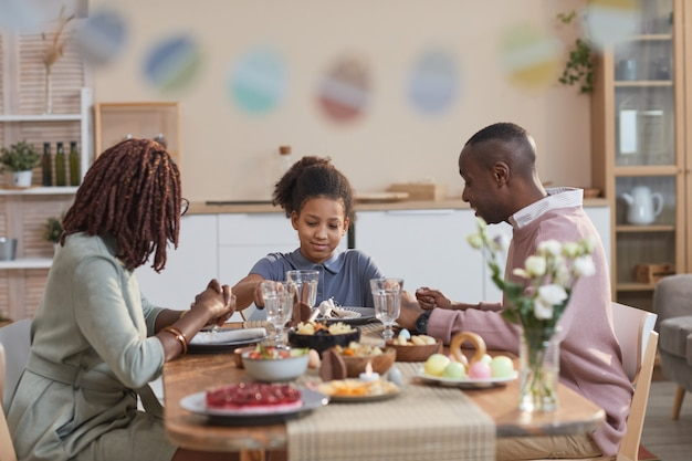 Portrait of modern african -american family enjoying dinner together while celebrating easter at home, focus on smiling teenage girl in center, copy space