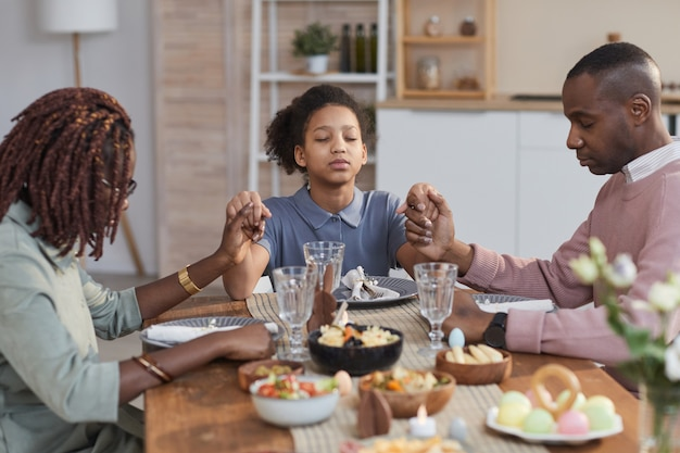 Portrait of modern african-american family saying grace at dinner table on easter and holding hands, copy space