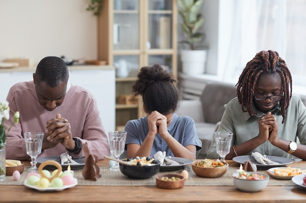 Portrait of modern african-american family saying grace at dinner table while celebrating easter at home, copy space