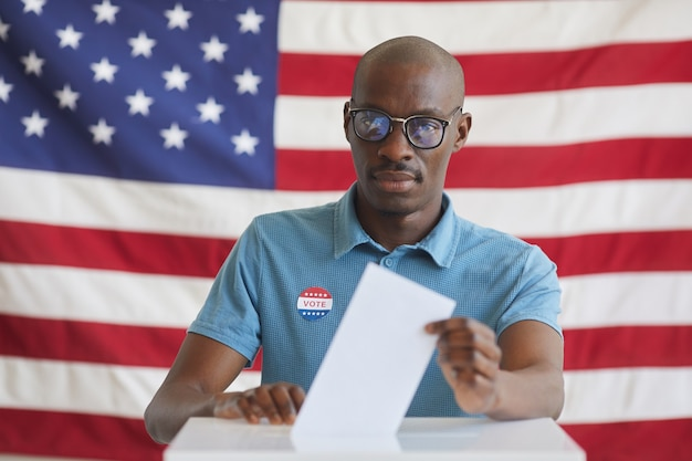 Portrait of modern african-american man putting vote bulletin in ballot box and  while standing against american flag on election day, copy space