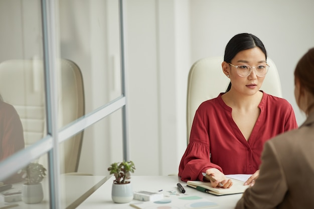 Portrait of modern asian businesswoman talking to client while working at desk in white office cubicle, copy space