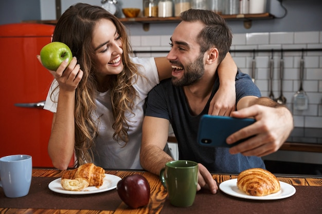 Portrait of modern couple man and woman taking selfie photo on cell phone while having breakfast in kitchen at home