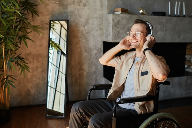 Portrait of modern disabled man in wheelchair enjoying music at home, copy space