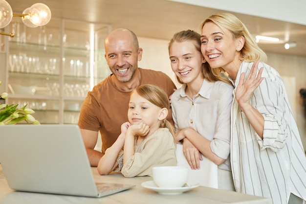 Portrait of modern happy family waving at camera while speaking by video chat with relatives