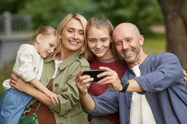 Portrait of modern happy family with two daughters taking selfie outdoors via smartphone while enjoying walk in green park