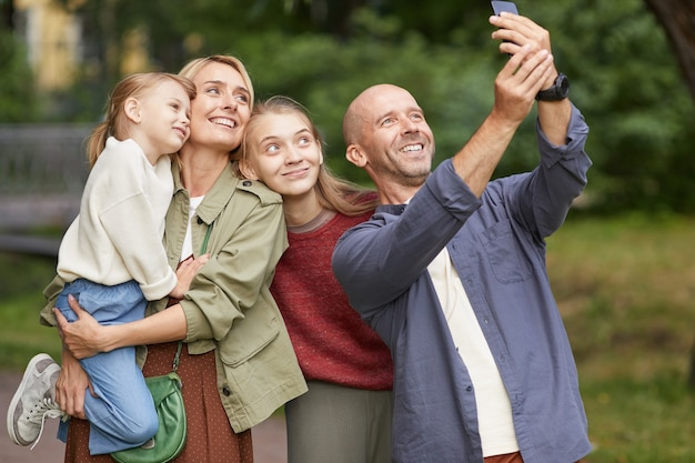 Portrait of modern happy family with two daughters taking selfie photo outdoors while enjoying walk in green park