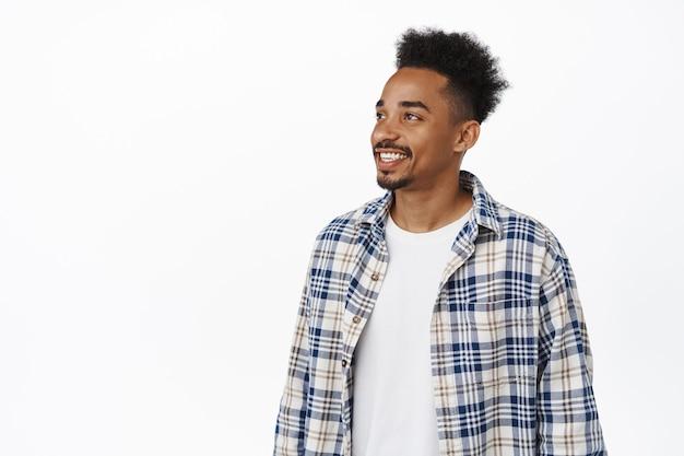 Ritratto di un moderno hipster con acconciatura afro e baffi, guardando da parte il banner di vendita, fissando a sinistra e sorridendo felice, guardando smth interessante, testo promozionale su uno spazio vuoto