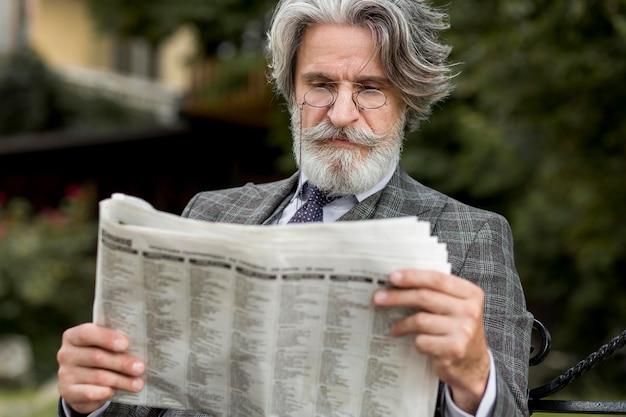 Portrait of modern man reading newspaper