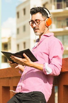 Portrait of a modern man standing against wall listening music on headphone reading the book