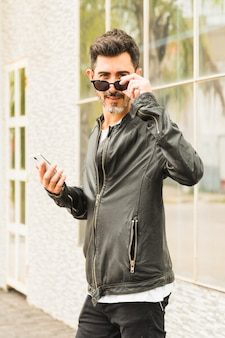 Portrait of modern man wearing black sunglasses holding smart phone in hand looking at camera