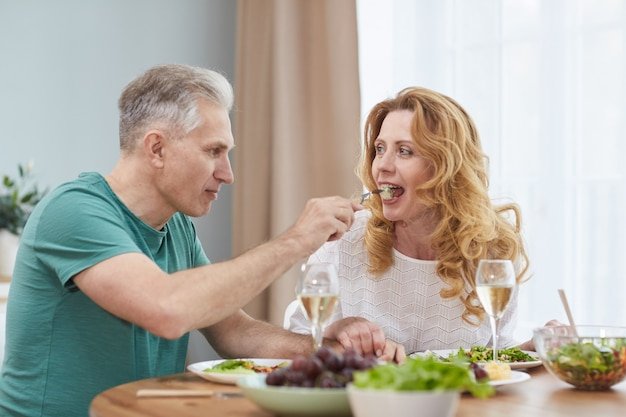 Portrait of modern mature couple enjoying dinner together at home, man giving wife piece of food on fork, copy space