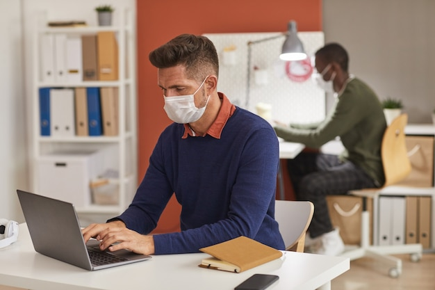 Portrait of modern mature man wearing mask and using laptop while working at desk in office, copy space