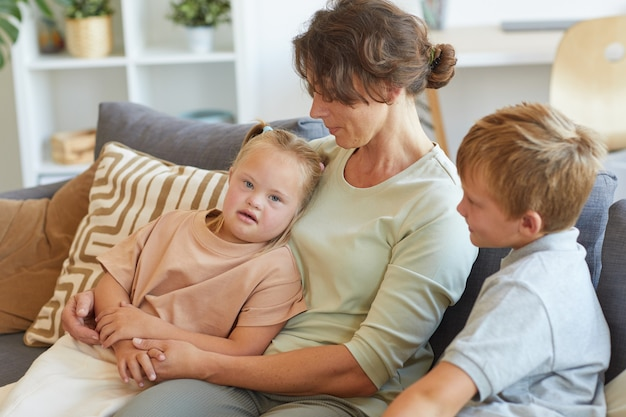 Portrait of modern mother embracing girl with down syndrome while sitting on couch with two kids in home interior
