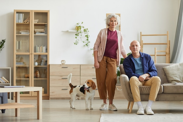 Portrait of modern senior couple posing in cozy home interior with pet dog