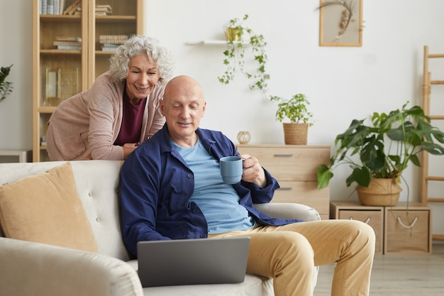 Portrait of modern senior couple smiling at laptop camera during video call with family