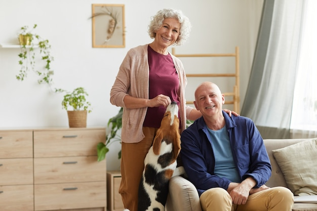 Portrait of modern senior couple smiling and posing in cozy home interior and playing with pet dog