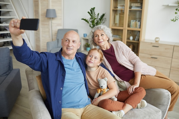 Portrait of modern senior couple taking selfie photo via smartphone with cute red haired girl in home interior