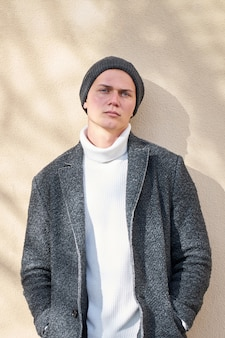 Portrait of modern urban young serious hipster stylish man wearing modern gray coat, white trendy sweater and black jeans