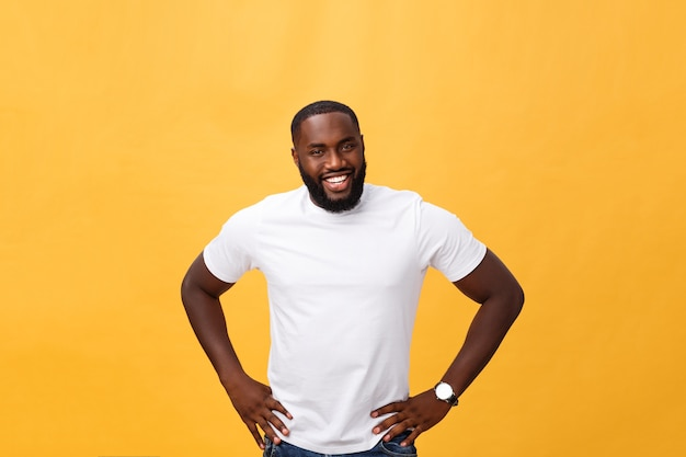 Portrait of a modern young black man smiling standing on isolated yellow background.