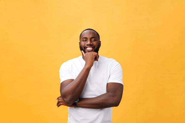 Portrait of a modern young black man smiling with arms crossed on isolated yellow background