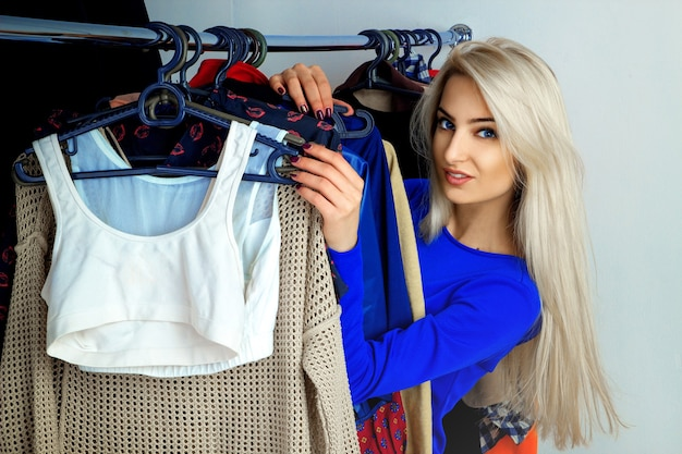 Portrait of modern young blonde girl with blue eyes and beautiful smile in clothing store
