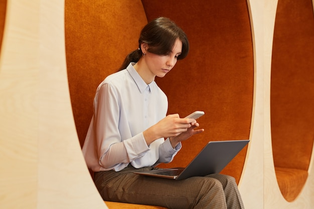 Portrait of modern young businesswoman using laptop and smartphone while working in open space office, sitting in graphic lounge zone, copy space