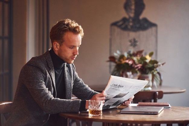 Portrait of modern young guy in formal clothes that sits in the cafe and reads newspaper.