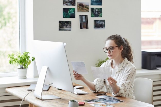 Portrait of modern young woman holding photographs reviewing for publishing while working at pc in white office, copy space