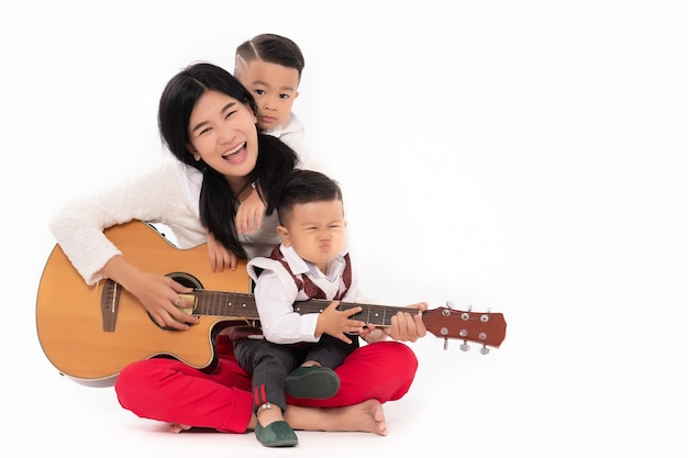 Portrait of mom playing guitar with sons on white