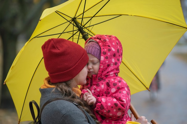 Portrait of mom who hugs her little daughter holding her in her arms under yellow umbrella in a yellow autumn park.