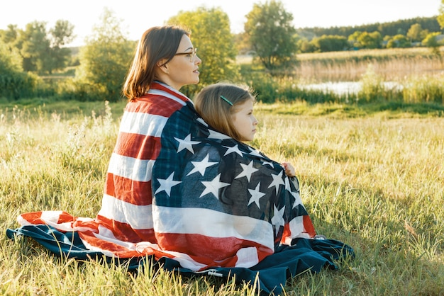 Portrait of mother and child daughter with american flag