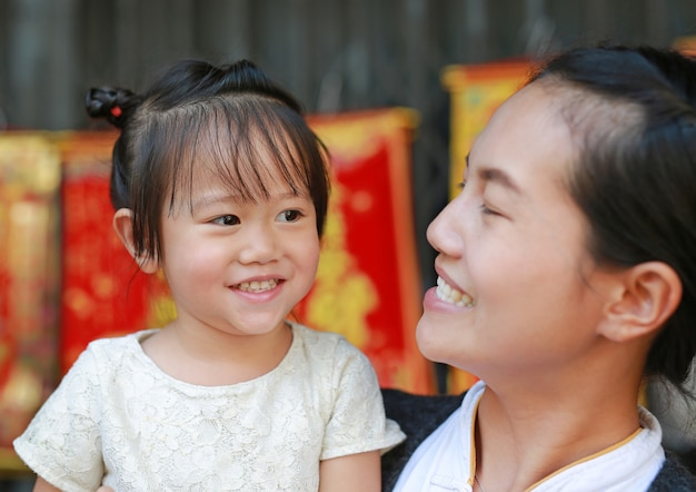 Portrait of mother and cute little girl in yaowarat road (bangkok chinatown) at chinese new year
