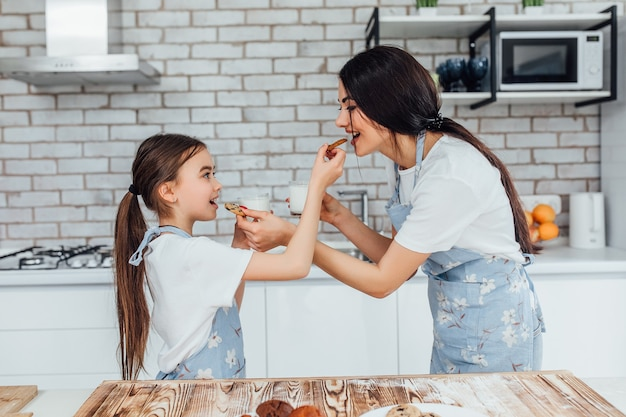 Portrait of mother and daughter eating breakfast