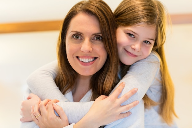 Portrait of mother and daughter embracing each other