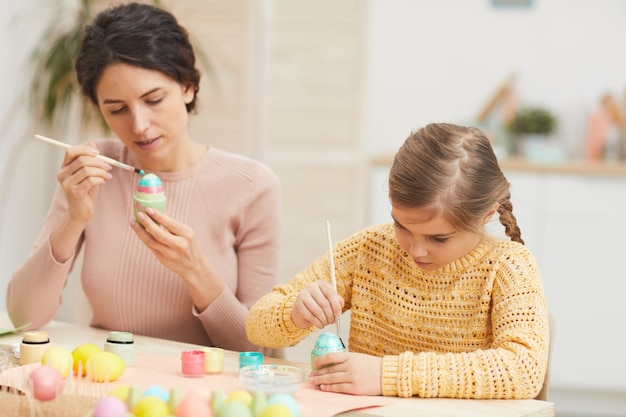 Portrait of mother and daughter painting easter eggs together sitting at table in cozy kitchen interior, copy space