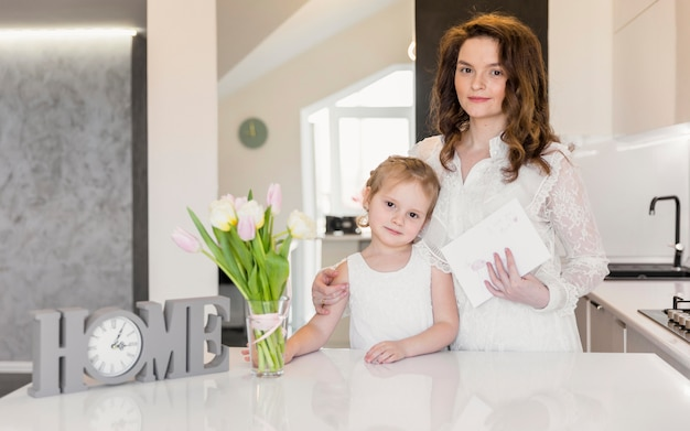 Portrait of mother and daughter standing near white dinning table