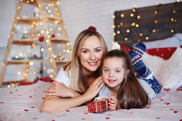 Portrait of mother and daughter with christmas present