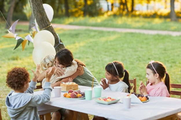 Portrait of mother embracing little son during birthday party outdoors with friends copy space