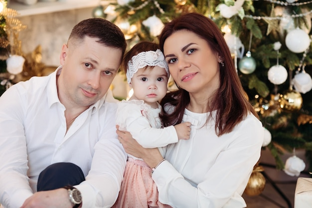 Portrait of mother, father and lovely baby girl smiling at front sitting by decorated christmas tree with christmas balls