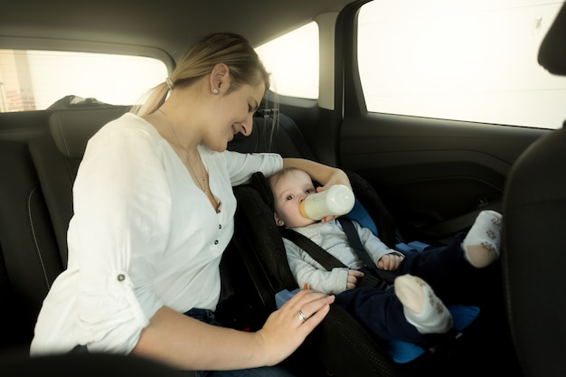 Portrait of mother feeding baby in car safety seat