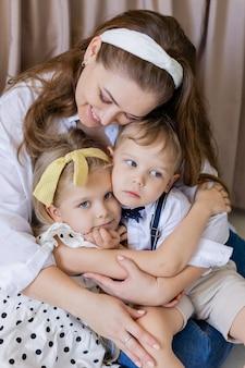 肖像画の母親は優しく彼女の子供たちを抱きしめます幸せな女の子と男の子はお互いと彼らの母親を抱きしめます