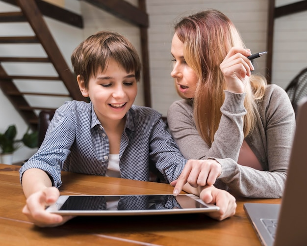 Portrait of mother helping son with homework