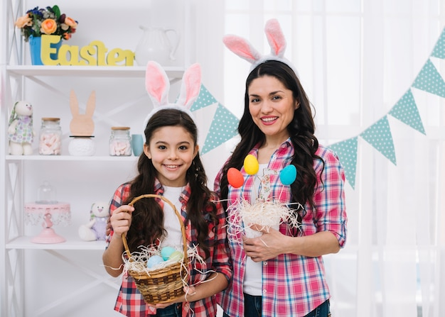 Portrait of mother and her daughter holding colorful easter eggs in hand