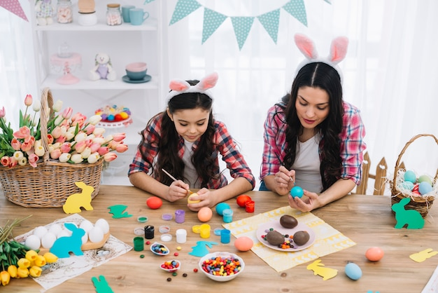 Portrait of mother and her daughter painting the easter eggs with brush on table