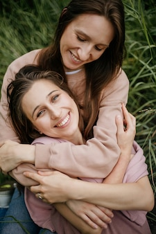 Portrait of mother hugging beautiful adult daughter, sitting on green grass, dressed in beige sweaters