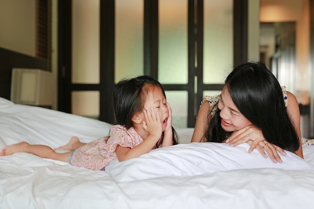 Portrait of mother and little asian girl lying on bed at the morning. little girl is yawni