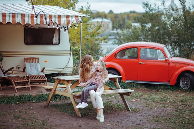 Portrait of mother and little daughter hugging and relaxing in countryside on camper van vacation with red retro car