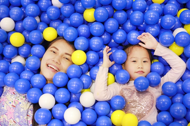 Portrait of mother and little girl playing with color plastic balls playground.