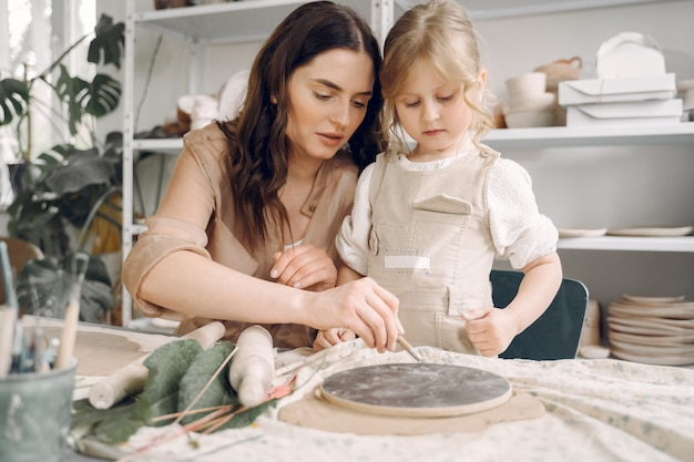 Portrait of mother and little girl shaping clay together