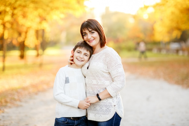 Portrait of a mother and son at autumn park